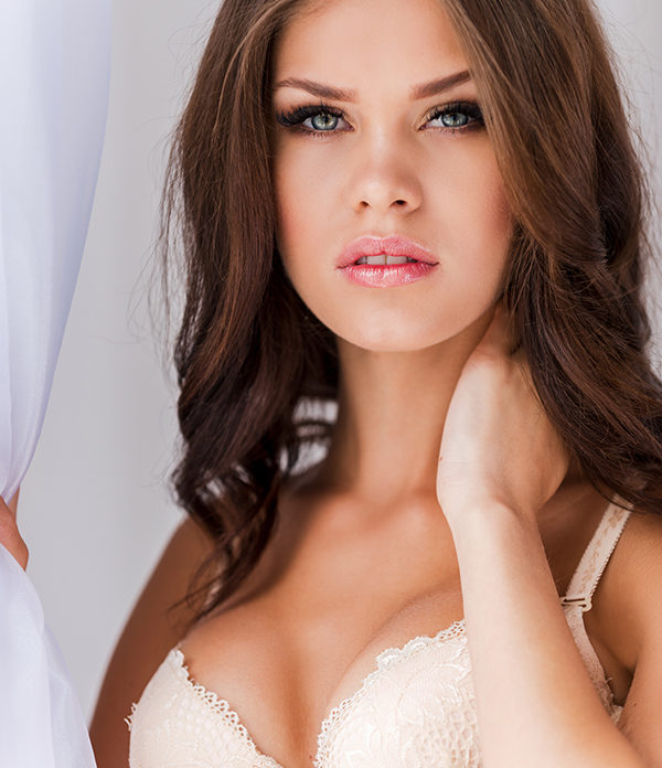 Pure beauty. Beautiful young woman in bra touching her neck and looking at camera while standing near the window