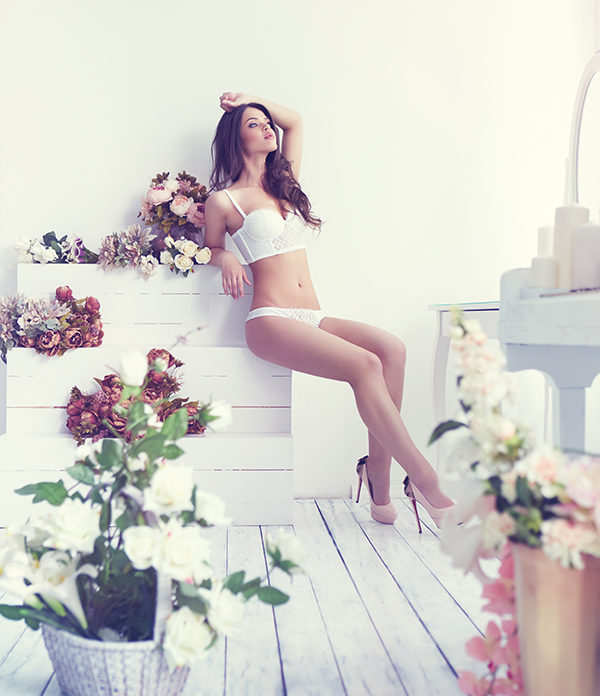 Beautiful young woman in white sexy lingerie posing indoor among lots of flowers
